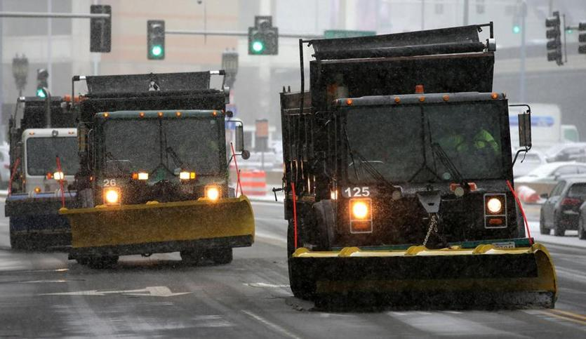 Plows lined up on Congress Street in swirling snow as the storm began.